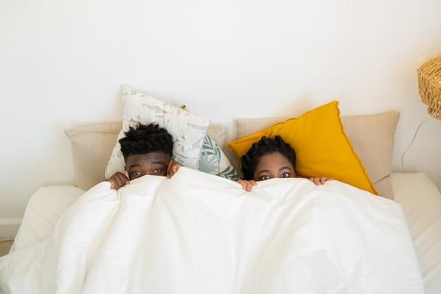 Schönes junges afrikanisches paar, das unter einer decke schläft