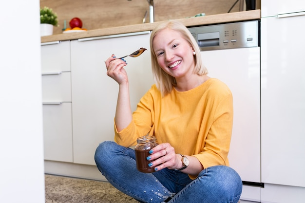 Schönes junges albino-mädchen in der freizeitkleidung, die köstlichen schokoladenaufstrich schmeckt, während auf dem holzboden in der heimischen küche sitzt.