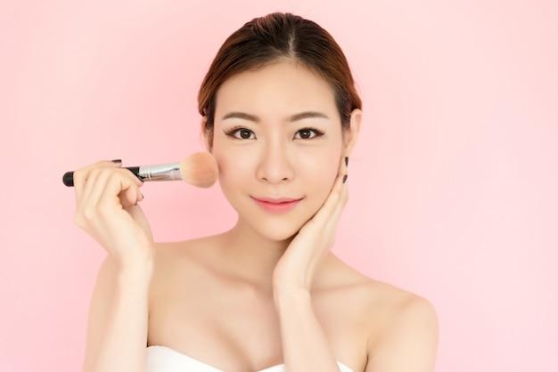 Schönes junges asiatisches frauengesicht der nahaufnahme lokalisiert auf rosa