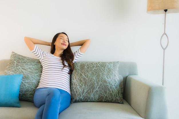 Schönes junges asiatisches frauenlächeln des porträts glücklich auf sofa
