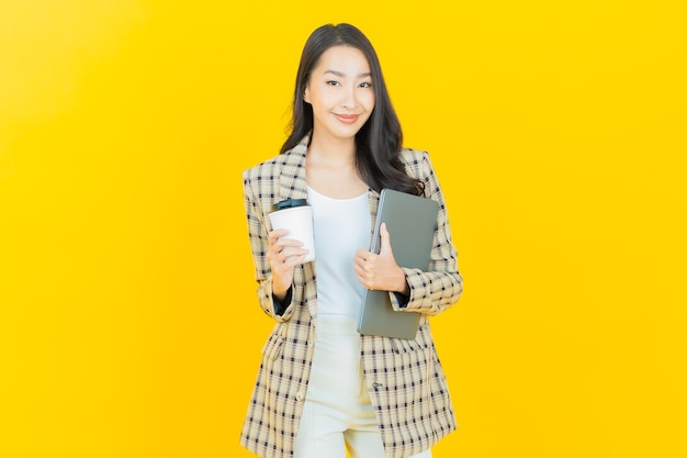 Schönes junges asiatisches frauenlächeln des porträts mit computerlaptop