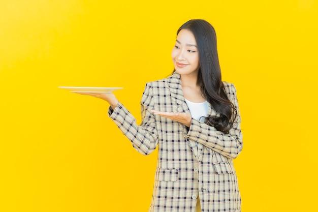 Schönes junges asiatisches frauenlächeln des porträts mit leerem tellerteller