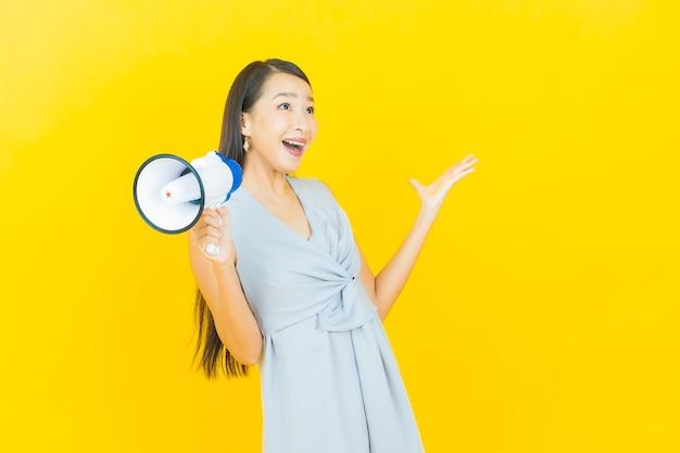Schönes junges asiatisches frauenlächeln des porträts mit megaphon