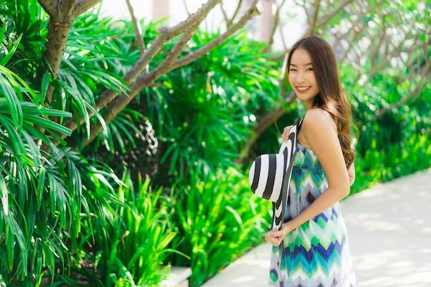 Schönes junges asiatisches frauenlächeln des porträts und glücklich um garten im freien