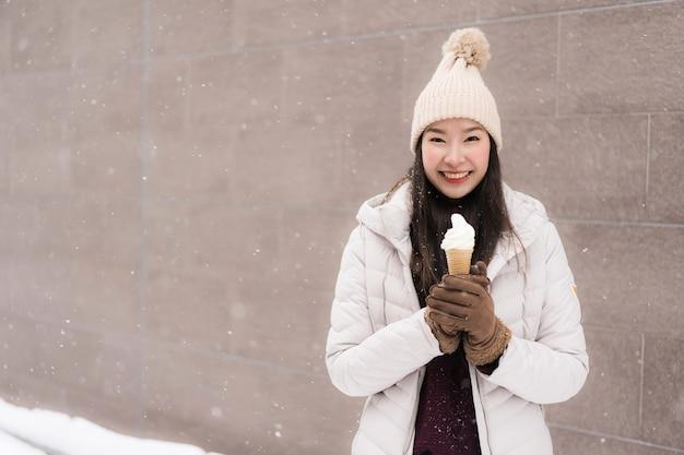 Schönes junges asiatisches frauenlächeln und glücklich mit eiscreme in der schneewintersaison
