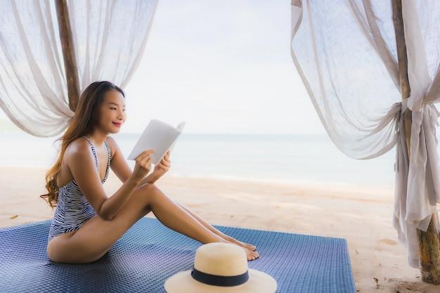 Schönes junges asiatisches frauenlesebuch des porträts mit glücklichem lächeln entspannen sich im klubsessel auf dem strandseeozean für freizeit