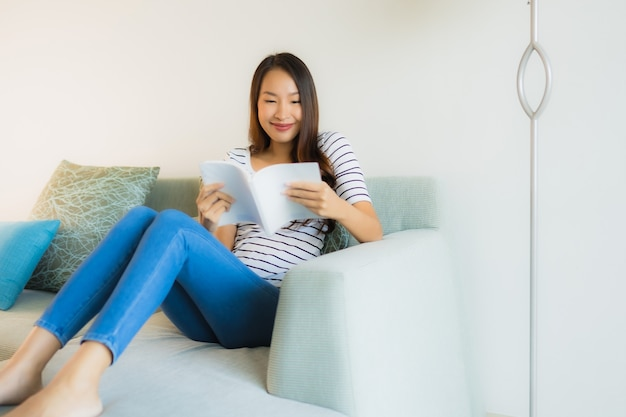 Schönes junges asiatisches frauenlesebuch des porträts mit kaffeetasse