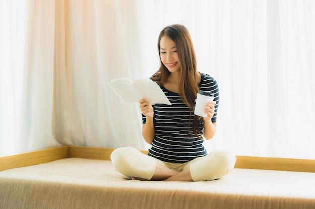 Schönes junges asiatisches frauenlesebuch des porträts und griffkaffeetasse oder -becher herein auf sofa im wohnzimmerbereich