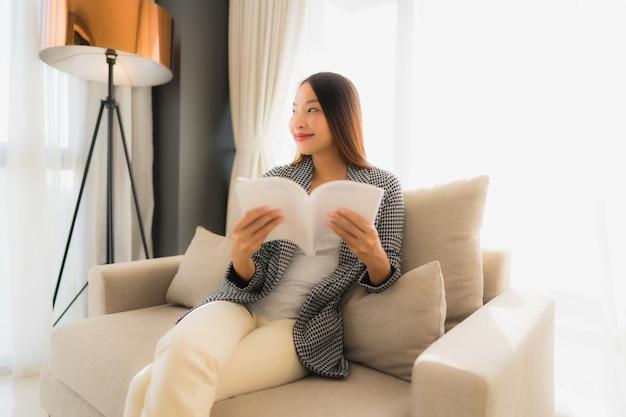Schönes junges asiatisches frauenlesebuch des porträts und sitzen auf sofastuhl