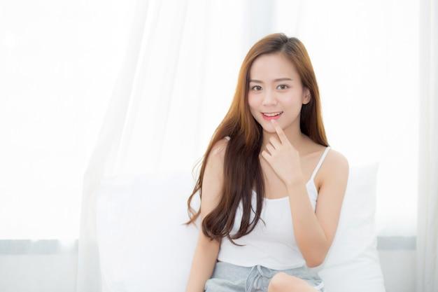Schönes junges asiatisches frauensitzen des porträts und lächeln das fenster am schlafzimmer.