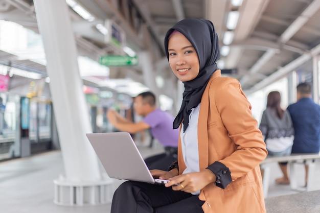 Schönes junges asiatisches mädchen, das an einem skytrain mit einem laptop arbeitet. muslimische frauen