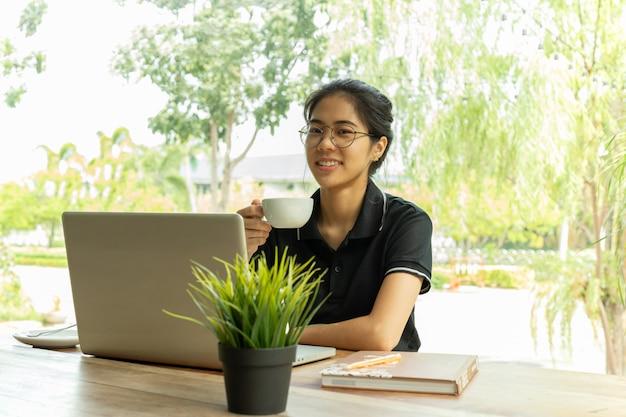 Schönes junges asiatisches mädchen, das auf dem tisch kaffee mit laptop am café hält.