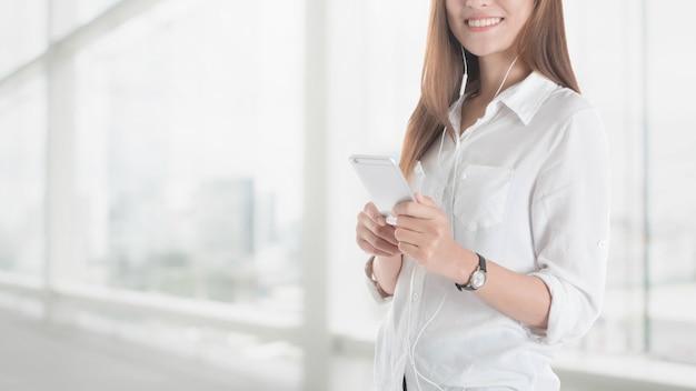 Schönes junges asiatisches mädchen, das intelligentes telefon mit hörmuschel im büro verwendet