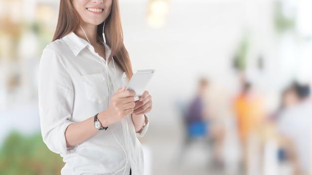 Schönes junges asiatisches mädchen, das intelligentes telefon mit hörmuschel im restauranthintergrund verwendet