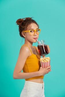 Schönes junges asiatisches mädchen, das popcorn hält und soda über blau trinkt.