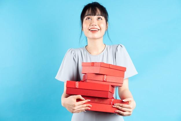Schönes junges asiatisches mädchen, das rote geschenkbox auf blau hält