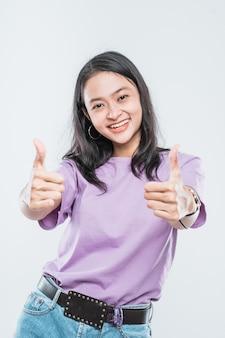 Schönes junges asiatisches mädchenmodell, das lächelt und zwei daumen oben zeigt