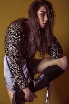 Schönes junges asiatisches modell in blauem jeansrock und schwarzer bluse und mode-make-up posiert auf trittleiter und schaut in die kamera. studioaufnahme. high-fashion-foto.
