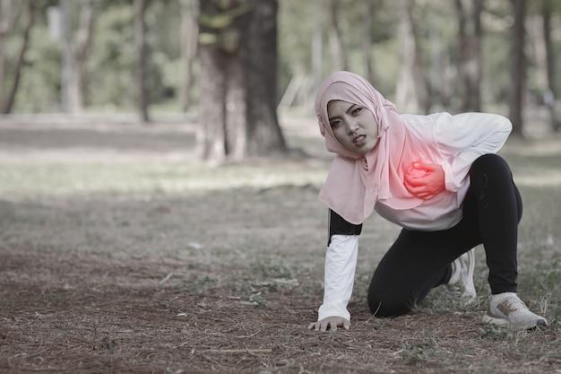 Schönes junges asiatisches muslimisches mädchen in sportkleidung hält nach langer übung die hände auf brust oder brust und schmerzen. fitness frau atemproblem und herzinfarkt fühlen. medizin- und sportkonzept