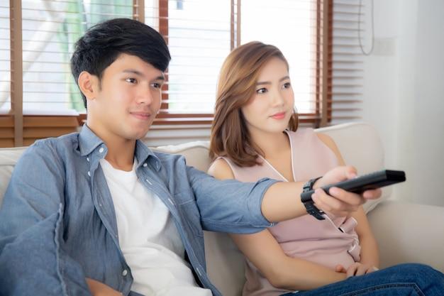 Schönes junges asiatisches paar, das fernbedienung hält und fernsieht