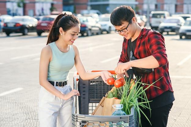 Schönes junges asiatisches paar, das gekauftes essen im einkaufswagen nahe dem großen laden prüft