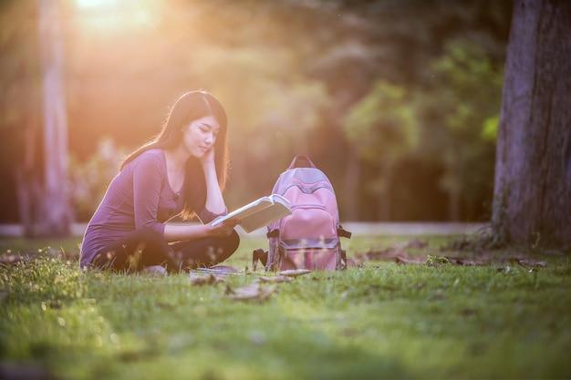 Schönes junges asiatisches schulmädchen, das ein buch liest