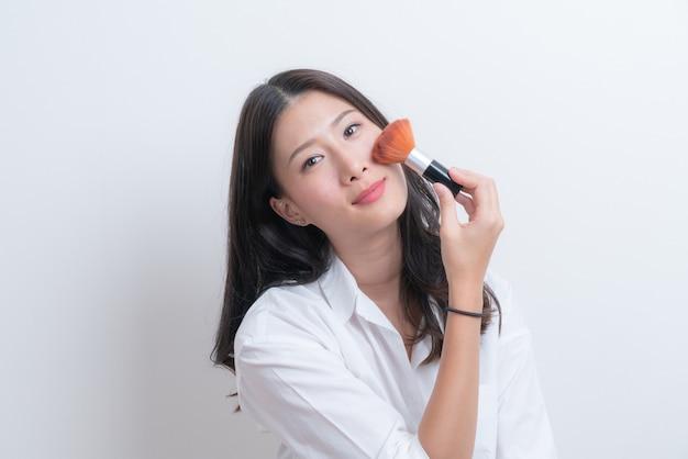 Schönes junges asiatisches weibliches modell, das erröten mit kosmetischem pinsel im weißen hemd setzt