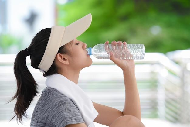 Schönes junges asien-frauen-trinkwasser nach der ausbildung.