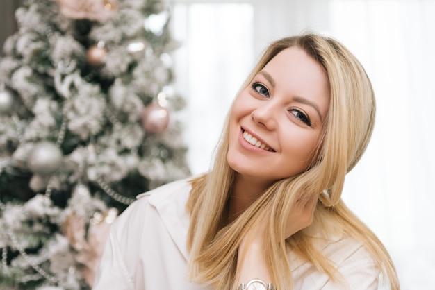 Schönes junges blondes lächelndes mädchen schmückt das haus für das neue jahr
