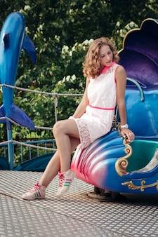 Schönes junges blondes mädchen, das parkkarussell genießt