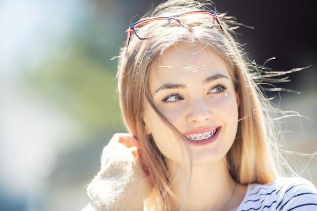 Schönes junges blondes mädchen, das zahnspangen trägt, lächelt und zur seite schaut.