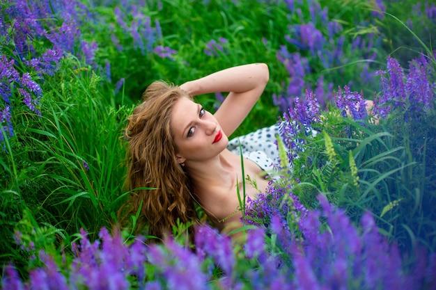 Schönes junges blondes mädchen in einem grünen feld unter lila wildblumen. schönes mädchen der tierwelt.