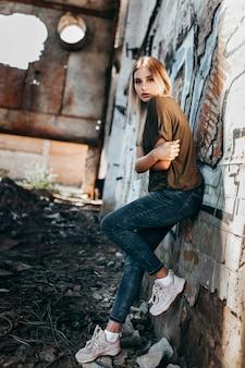 Schönes junges blondes mädchen in einem leeren grünen militärischen t-shirt