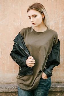 Schönes junges blondes mädchen in einem leeren grünen t-shirt und lederjacke