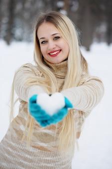 Schönes junges blondes mädchen mit einem herzen aus schnee in ihren händen
