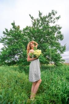 Schönes junges blondes mädchen sammelte einen strauß wildblumen. genießen sie einen spaziergang an einem warmen sommertag