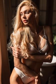 Schönes junges blondes mädchenmodell mit perfektem sexy körper in weißer spitzenwäsche steht am frühen morgen im badezimmer am fenster