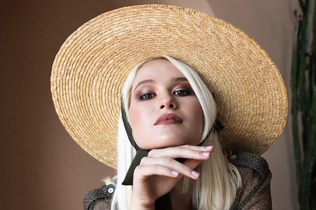 Schönes junges blondes modell posiert im strohhut und in der grünen transparenten bluse