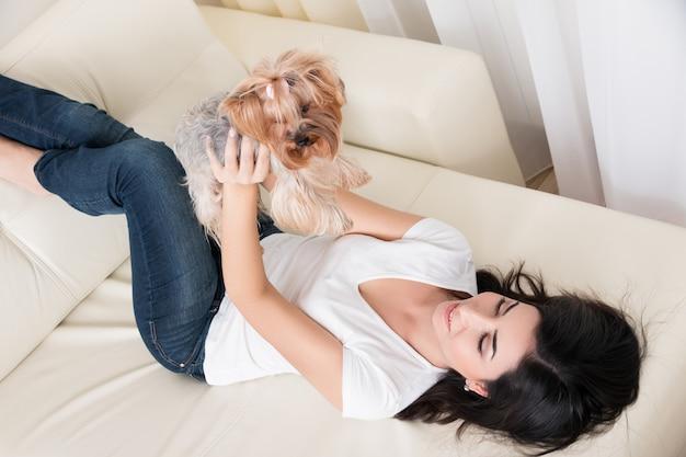 Schönes junges brünettes mädchen, das mit ihrem yorkshire terrier zu hause spielt, der am sofa niederlegt und ihr haustier hält