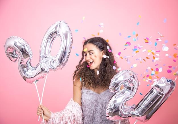 Schönes junges brünettes mädchen mit dem lockigen haar, das auf einer rosa wand mit konfetti aufwirft und in ihrer hand silberne luftballons für das neujahrskonzept hält