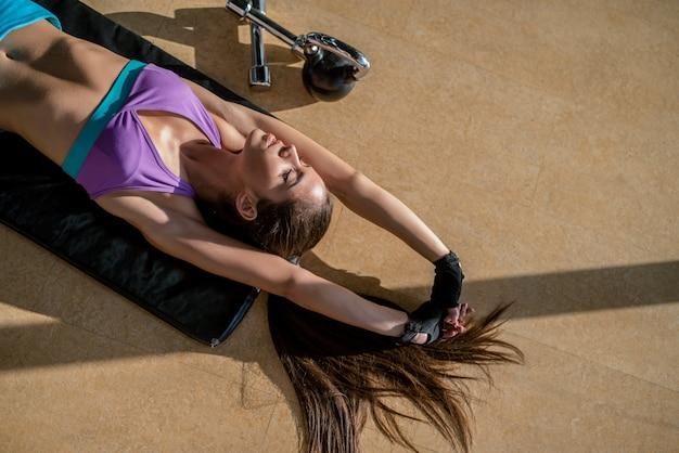 Schönes junges fit mädchen, das auf turnhallenboden liegt und ihre muskeln nach hartem training streckt.