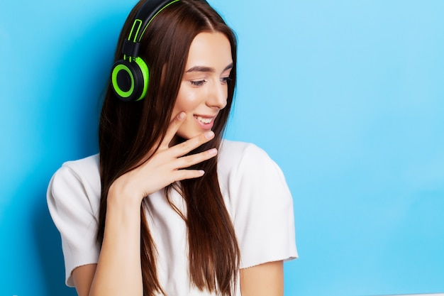 Schönes junges frauenmodell hört musik in kopfhörern auf blau