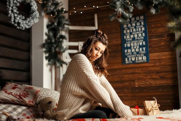 Schönes junges frauenmodell im weinlese-strickpullover mit geschenken auf dem bett mit weihnachtsdekorationen