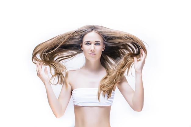 Schönes junges frauenmodell mit langem blondem haar und natürlichem make-up, das auf weiß aufwirft