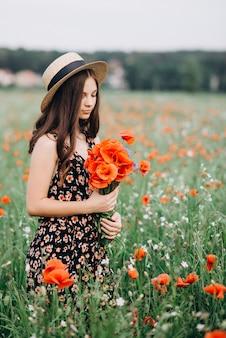 Schönes junges freies mädchen in einem hut in einem sommerfeld von roten mohnblumen mit einem blumenstrauß