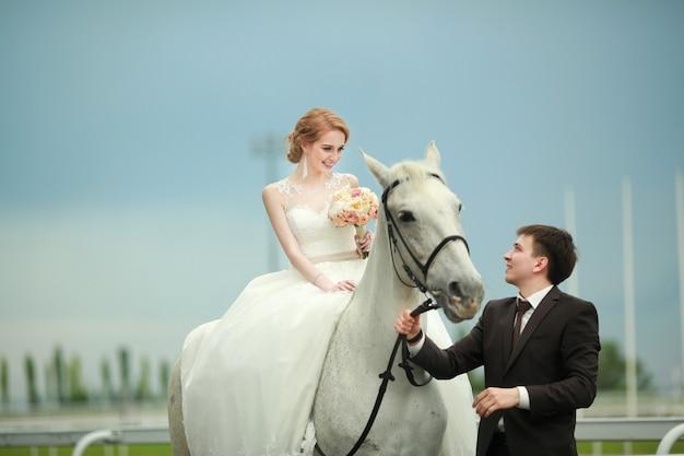 Schönes junges frisch verheiratetes paar auf einem spaziergang mit einem pferd