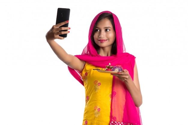 Schönes junges glückliches mädchen, das selfie mit pooja thali unter verwendung eines handys oder eines smartphone nimmt