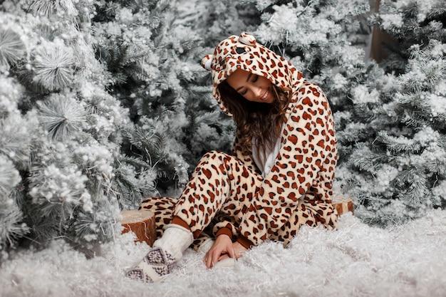Schönes junges glückliches mädchen im lustigen bärenpyjama, der nahe weihnachtsbaum mit schnee sitzt