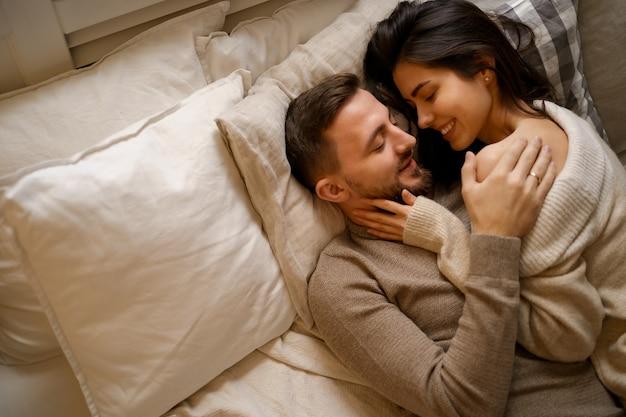 Schönes junges glückliches paar, das sich im bett entspannt und lächelt und umarmt