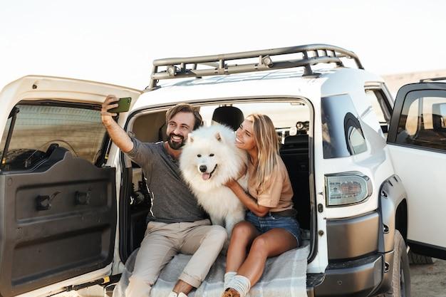 Schönes junges glückliches paar sitzt hinten in ihrem auto am strand und macht ein selfie beim spielen mit hund